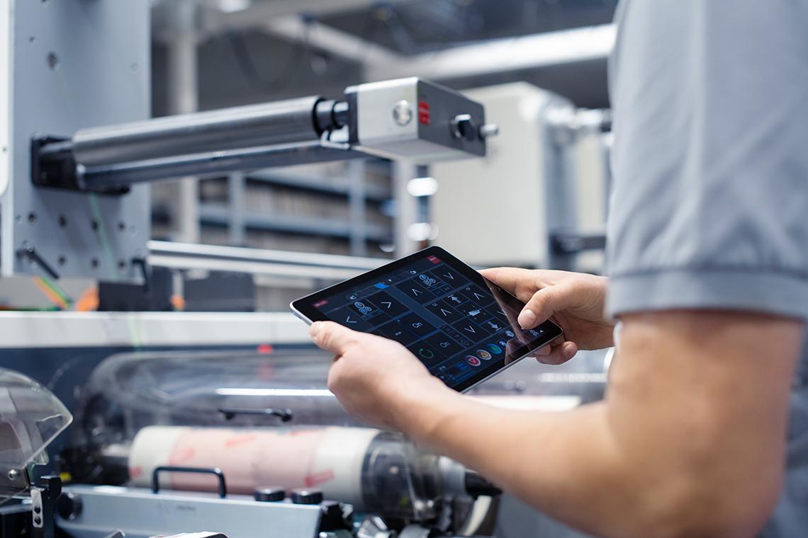 mitarbeiter-vor-flexodruckmaschine-mit-tablet